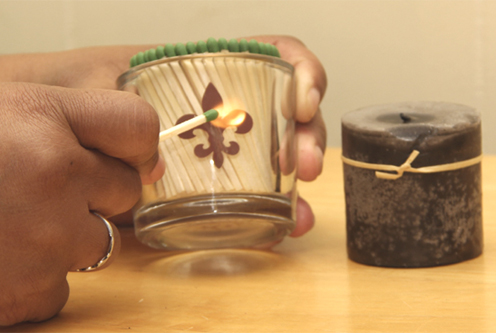 Glass Rectangle Match Holder with Fleur de Lis Striker, lighting a match, striking a match